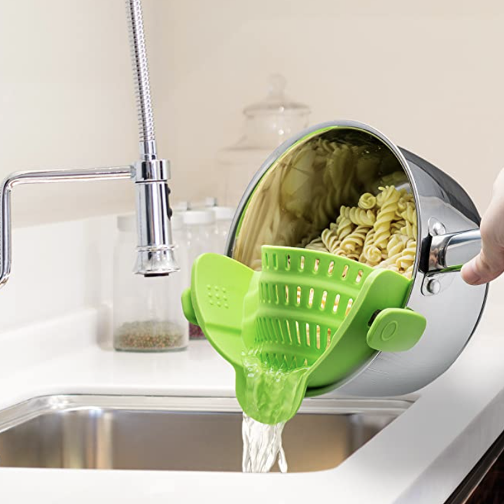 pasta water being drained with green strainer