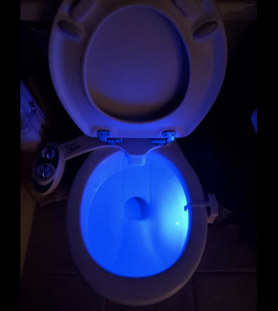 A toilet with a blue colored light