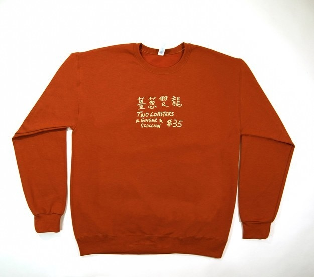 """A crew neck sweatshirt printed with Chines script and text that reads """"Two Lobsters w. Ginger + Scallion $35"""""""