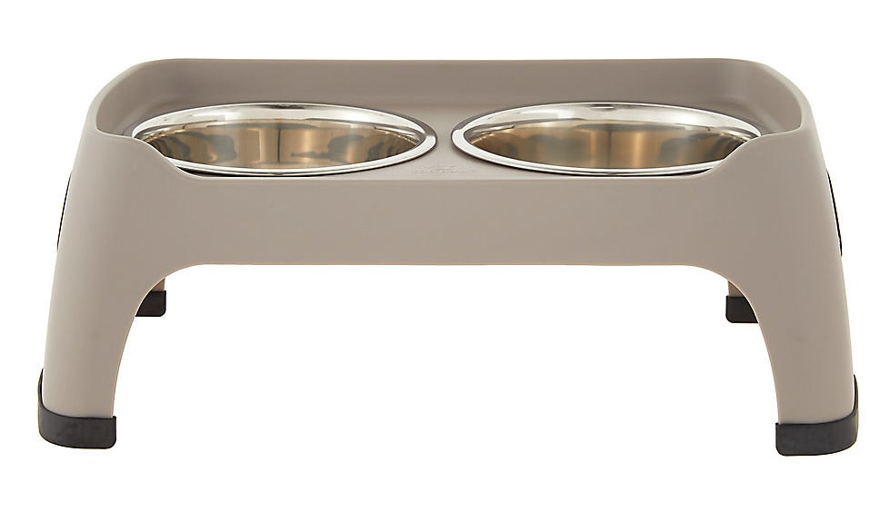 a tan elevated dog feeder with two bowls in it