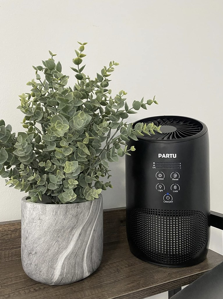 A black HEPA air purifier on a table next to a plant