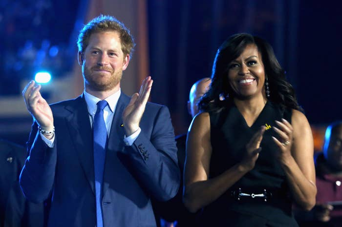 Michelle stands and claps next to Harry at an event