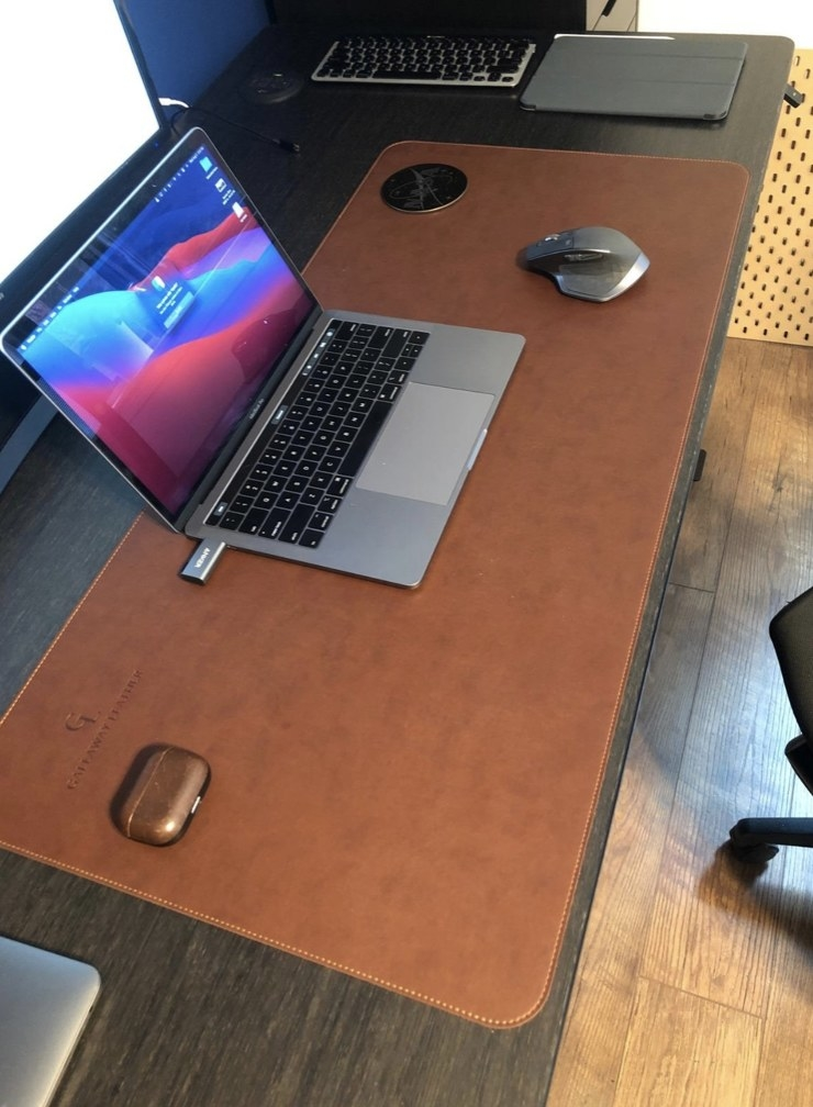 A brown desk pad with a laptop and desk accessories on top