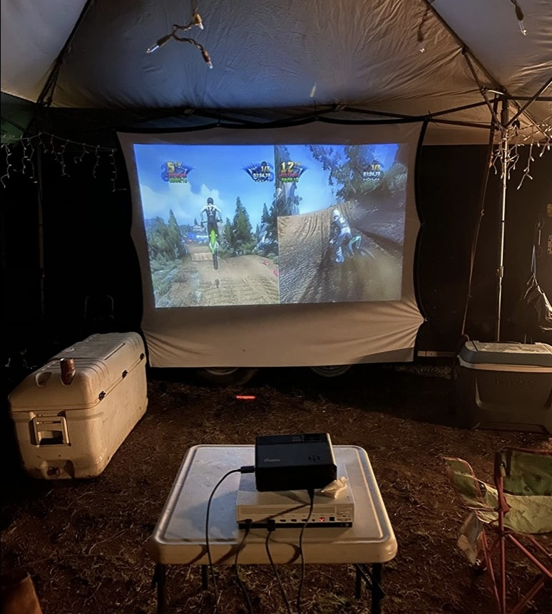 A mini projector setup outside in a yard, projecting a gam on a screen