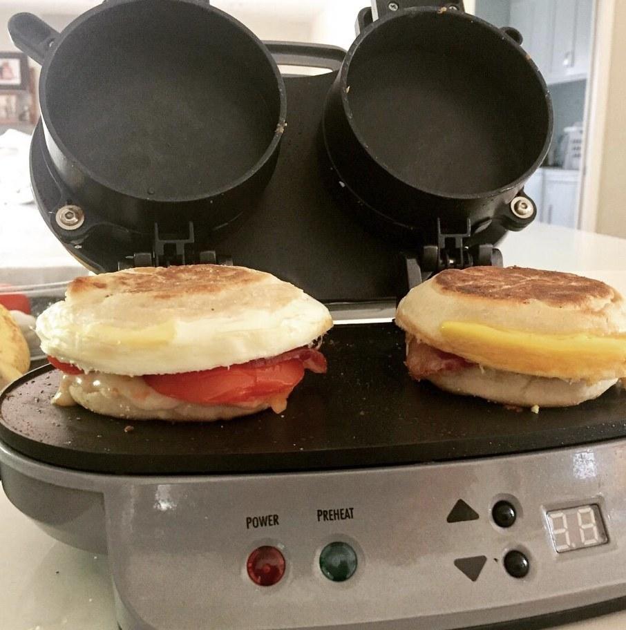 A breakfast sandwich maker with two sandwiches on it