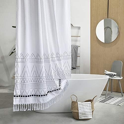 A white and black shower curtain in a bathroom