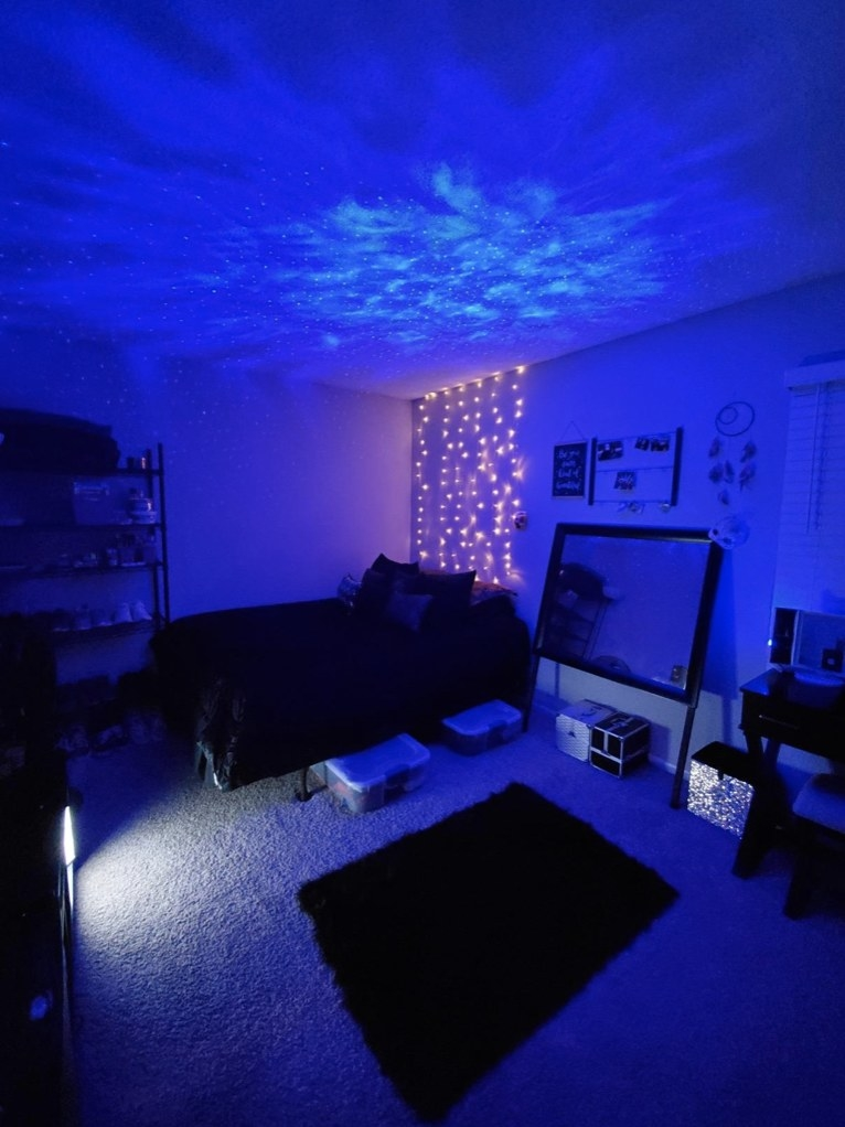 A bedroom lit up by a blue LED laser star projector