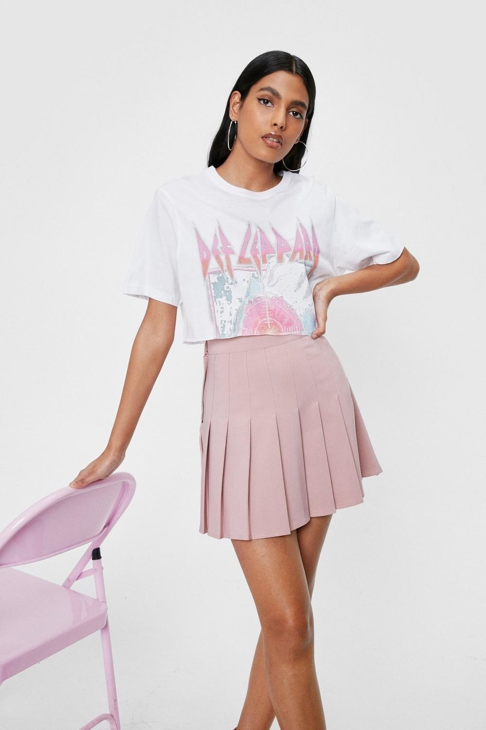 a model in a pink high waisted pleated skirt and a def leppard cropped tee