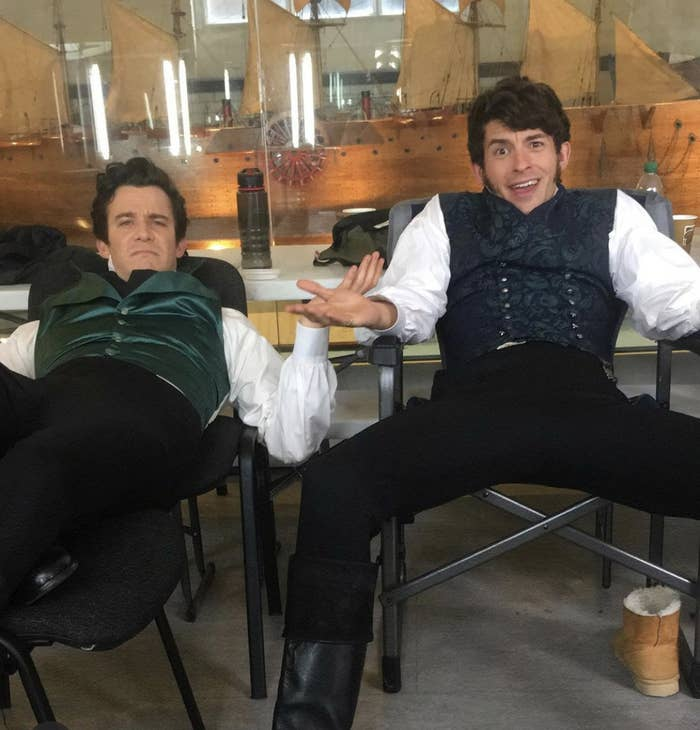 Luke Newton and Jonathan Bailey reclining on chairs on the set of Bridgerton
