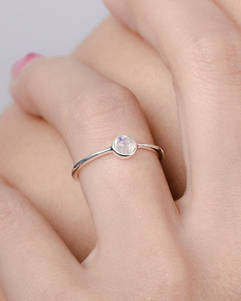 a thin band with a round moonstone in the middle