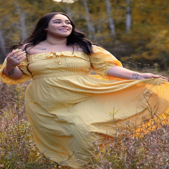 A reviewer wearing the dress in yellow in a field of flowers