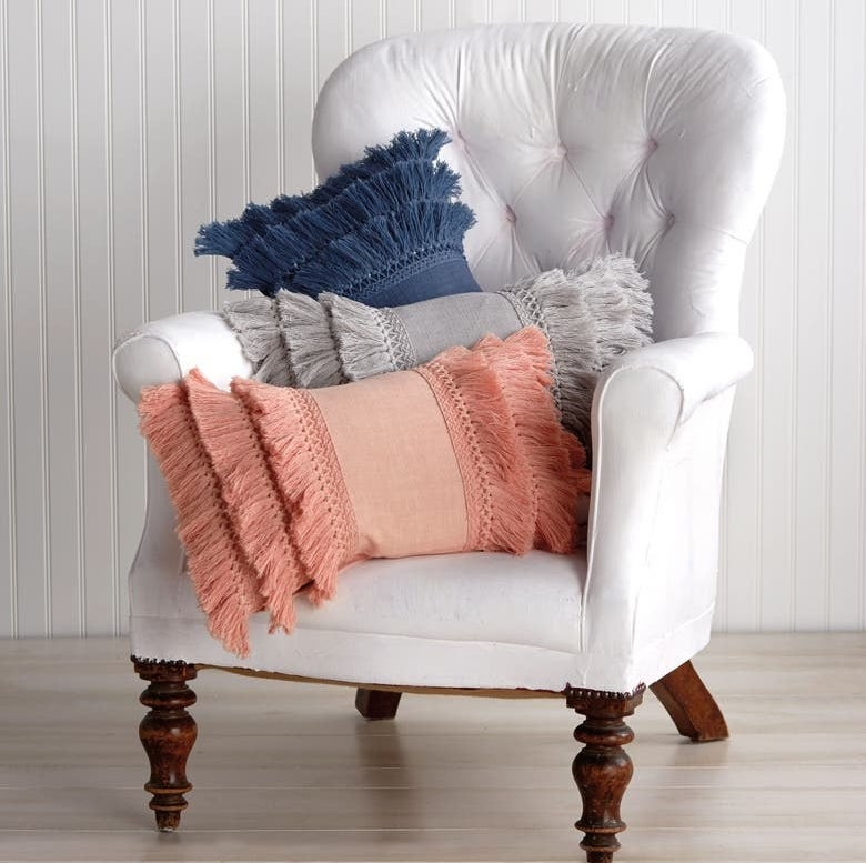 White chair holds pink, navy and gray fringe pillows