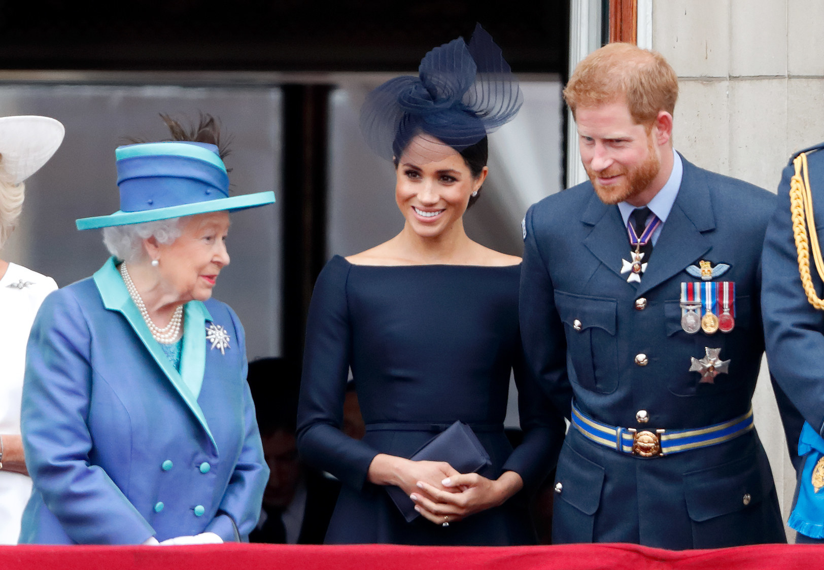 Harry and Meghan lean over to speak with the Queen at a formal event