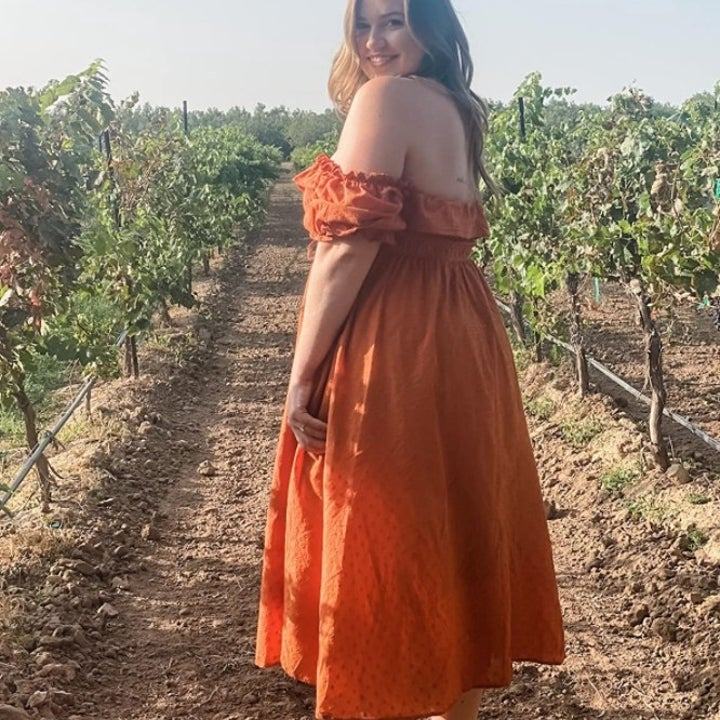 A reviewer wearing the dress in orange in an orchard