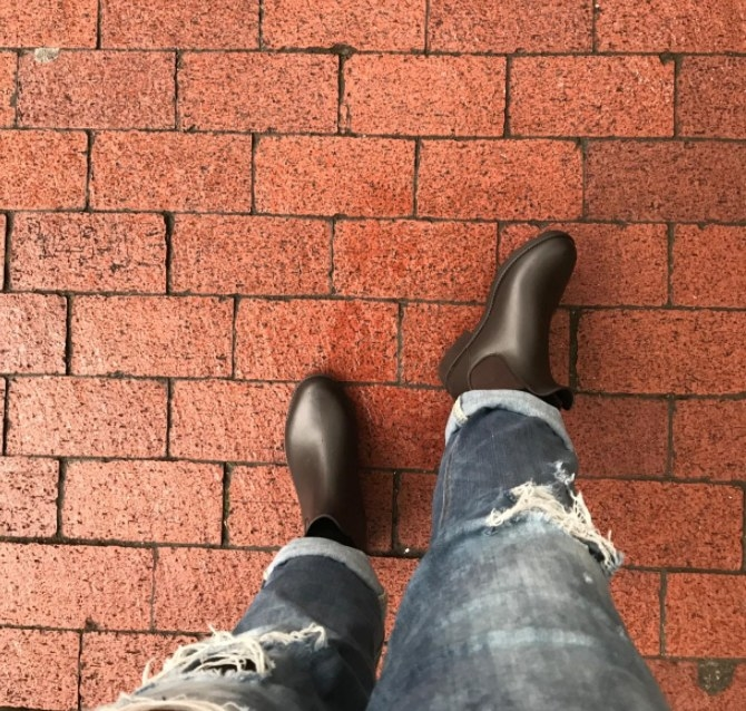 A reviewer wearing the boots in black against red brick