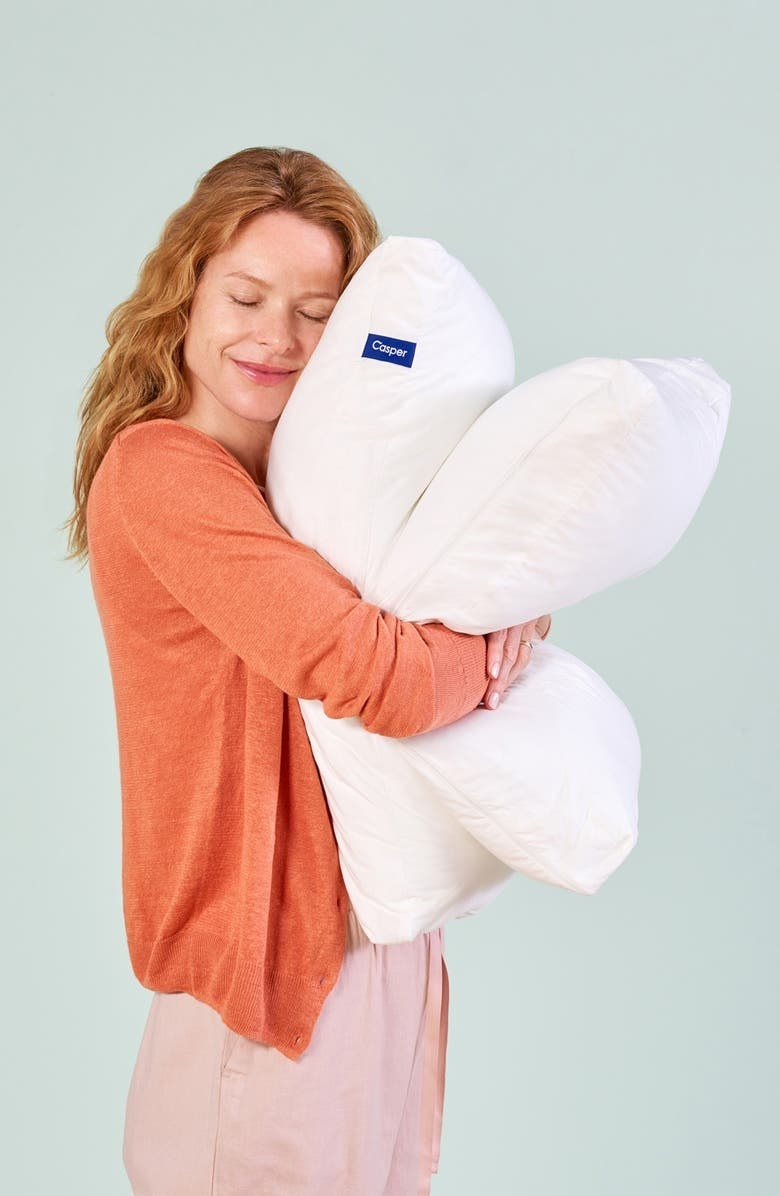 Model hugs two white casper pillows