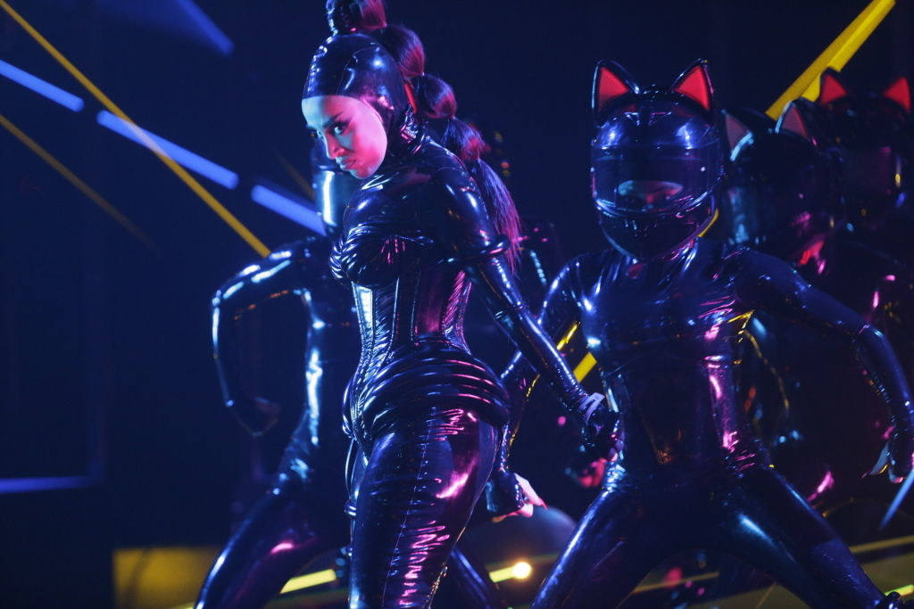 Doja Cat performing with her backup dancers in futuristic bodysuits