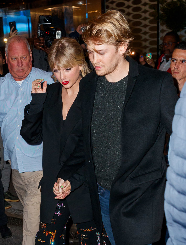 Taylor walking outside hand-in-hand with Joe