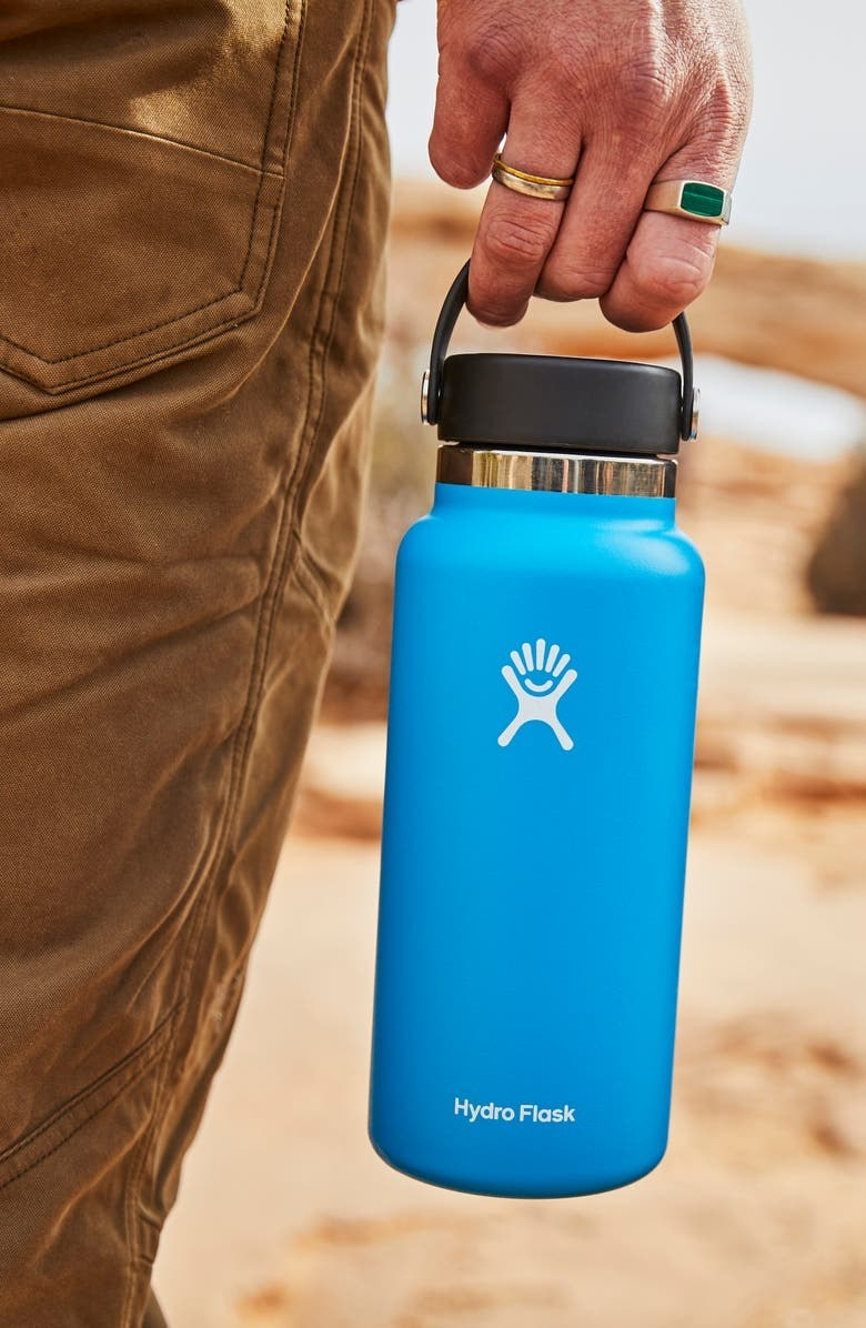 Model carries blue hydro flask with black lid and white details