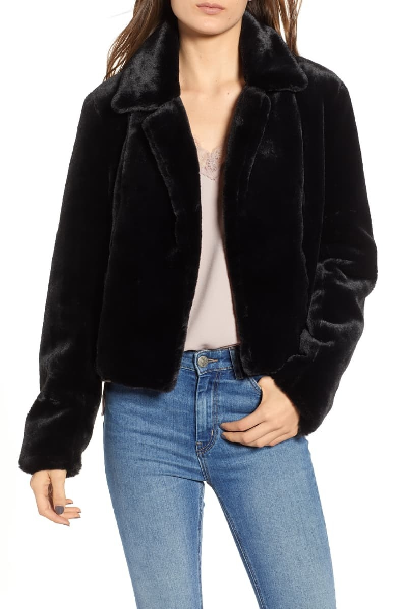 Model wears black faux fur jacket