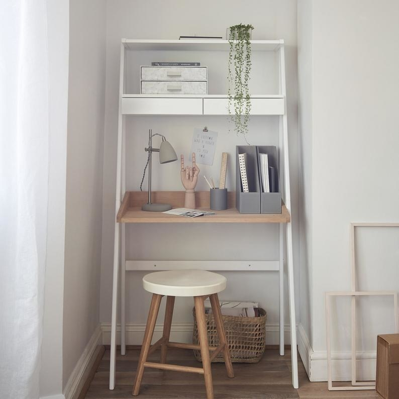 the ladder desk with plants on the tier shelves and wooden stool tucked under the desk