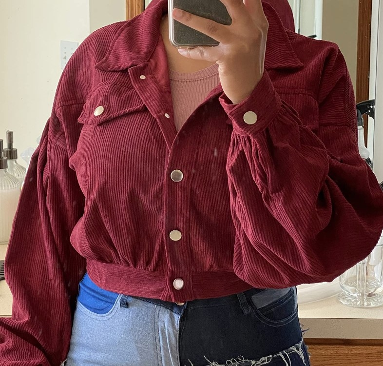 A reviewer wearing the jacket in burgundy