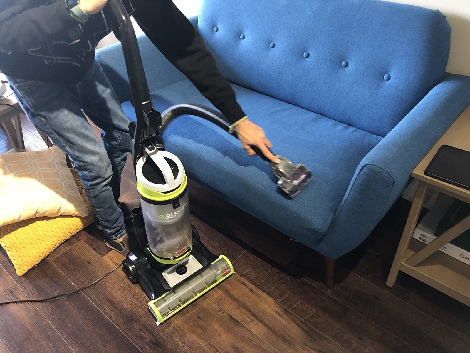 A reviewer uses the vacuum on a couch