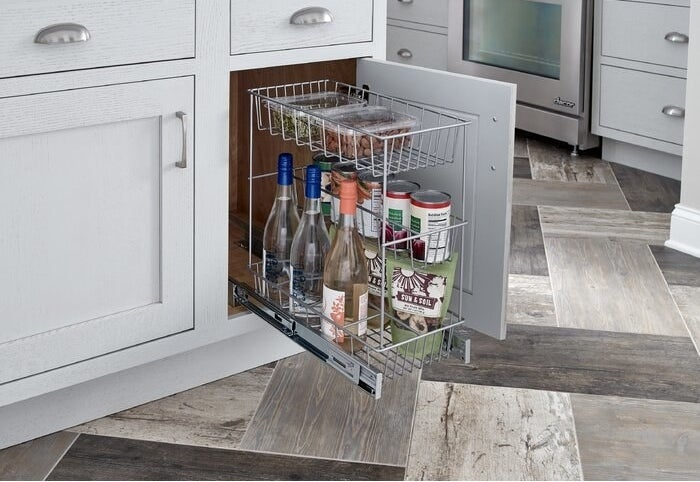 the pull out drawer in use in a kitchen holding cans and beverages