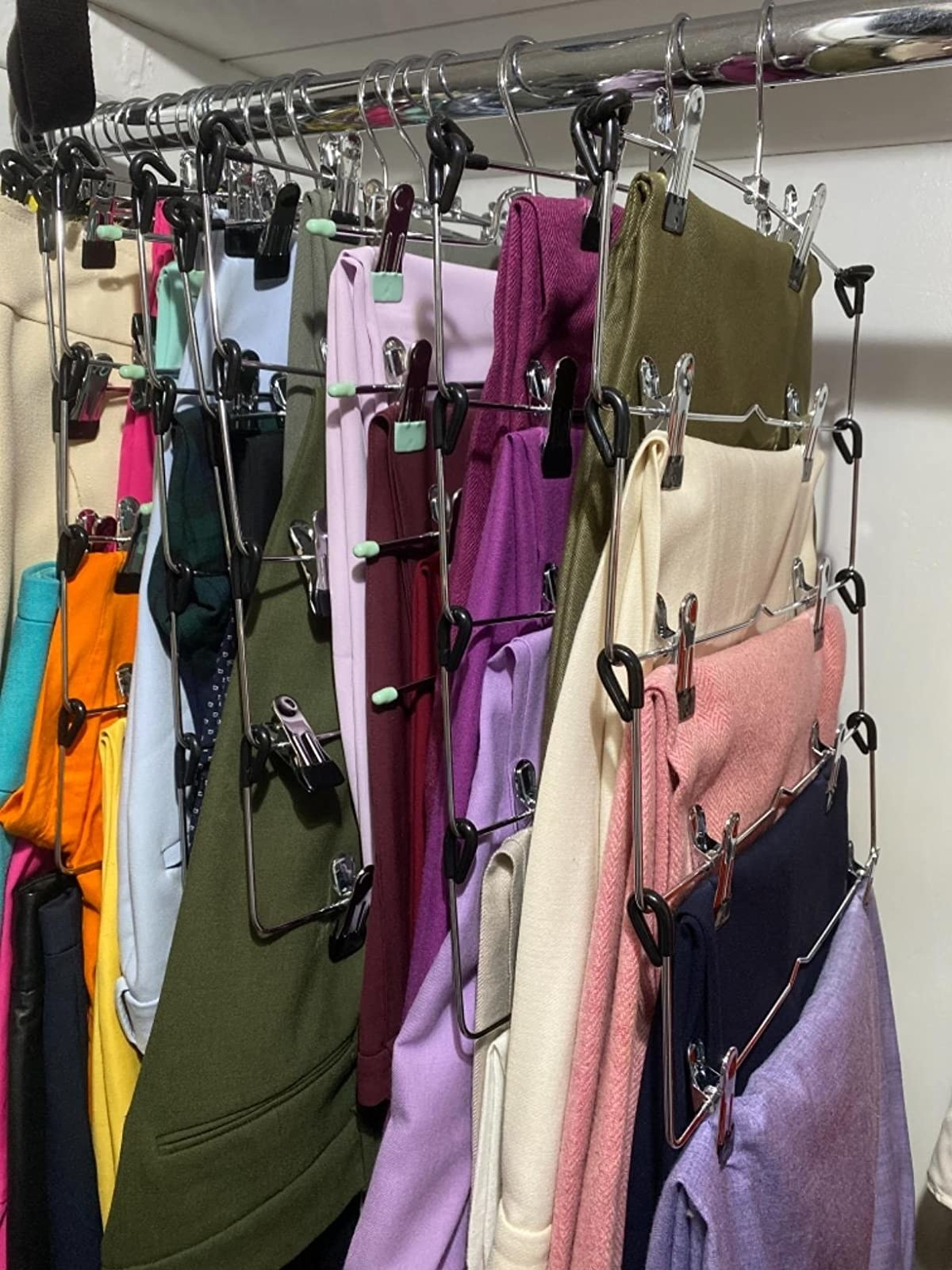 Reviewer photo of various clothing items hanging from skirt hanger
