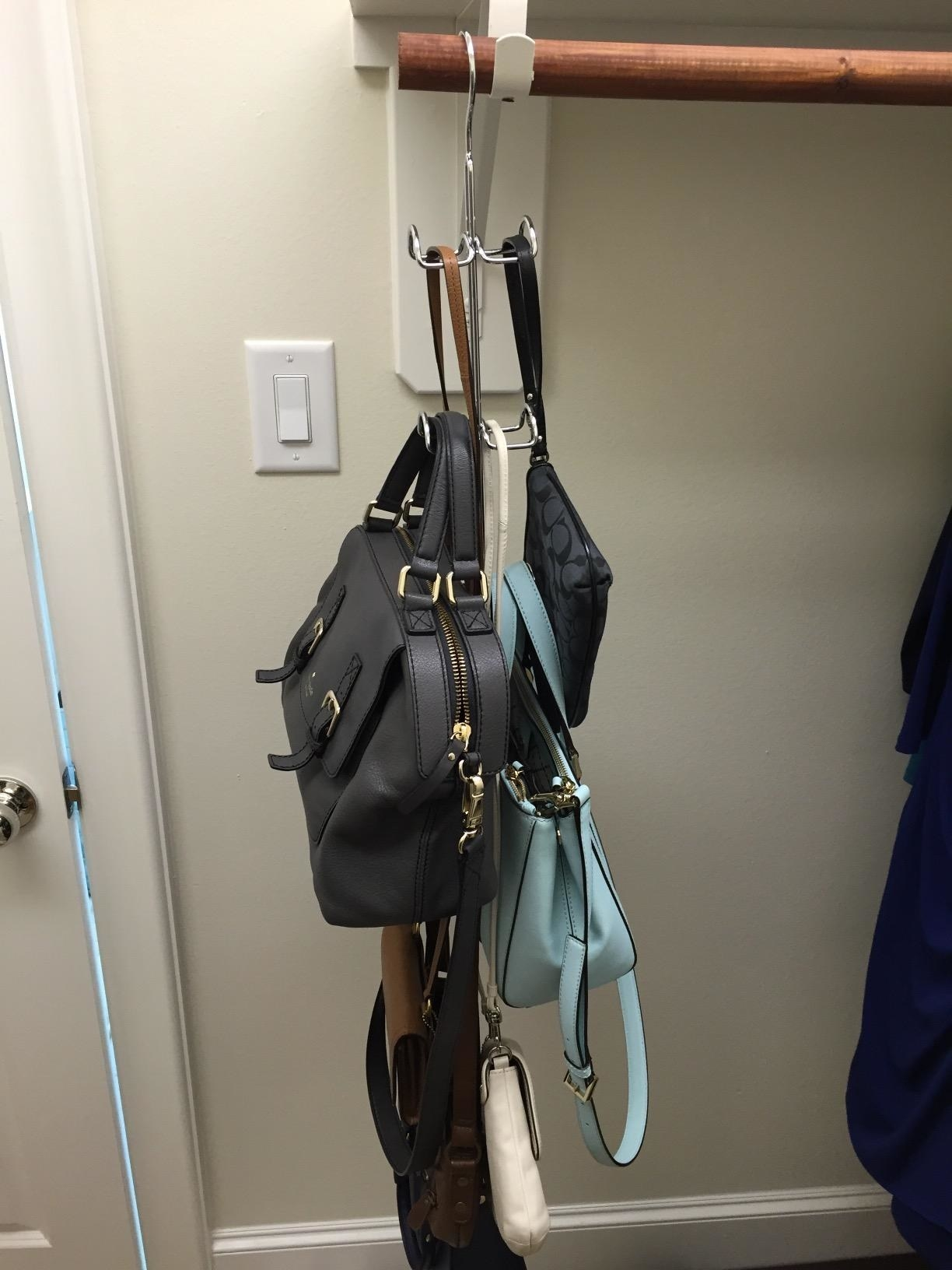 Reviewer photo of purses hanging from closet hook hanger