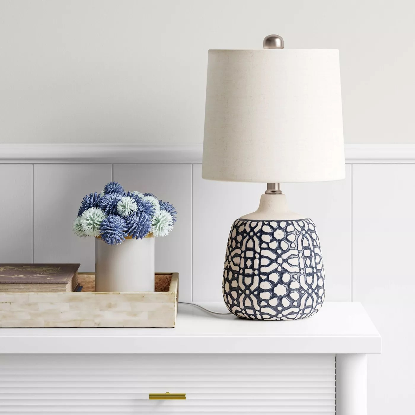 The lamp with a white shade and an intricate white and blue base on a table