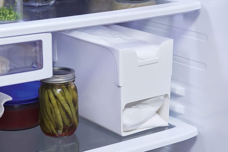 The milk bag dispensing organizer in a fridge beside a jar of green beans