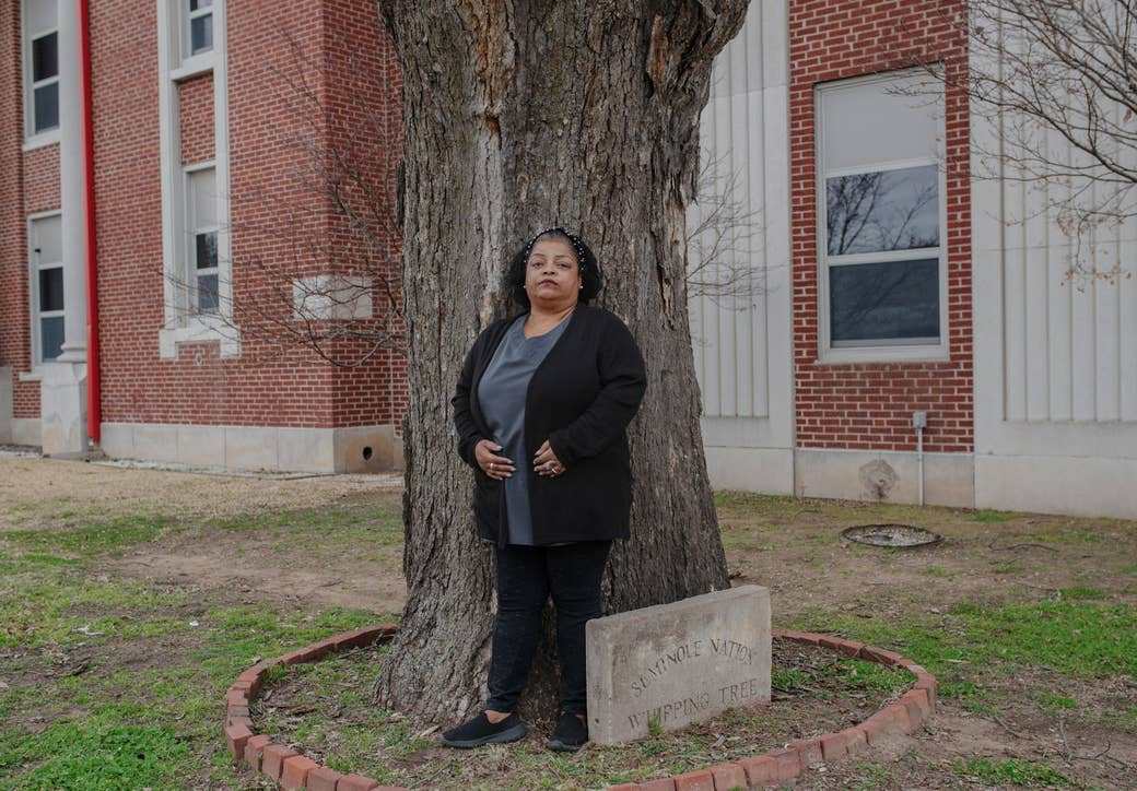 "A woman stands in front of a tree, marked with a cement sign that says ""Seminole Nation Whipping Tree"""