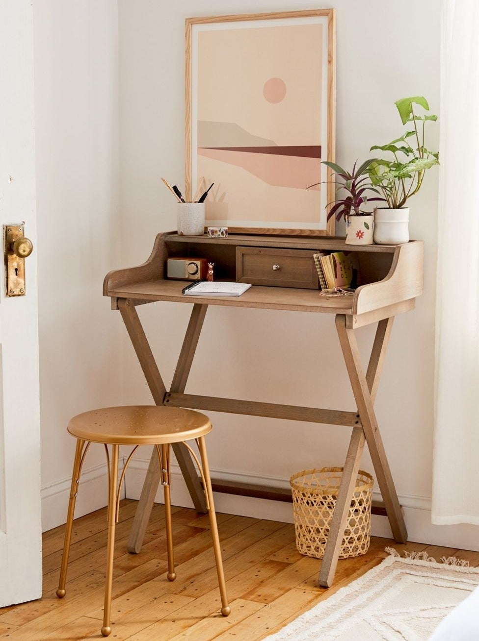 the cory folding desk in the corner of a room with plants and notebooks on its surface