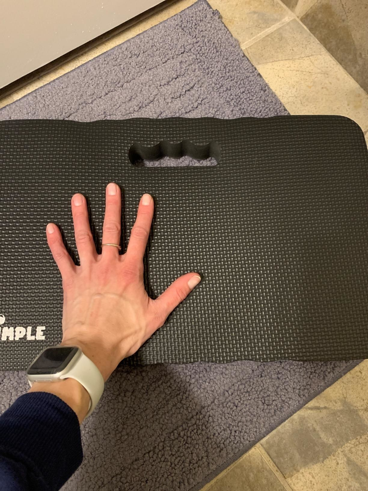 image of reviewer's hand atop the black dimple high density thick foam knee pad