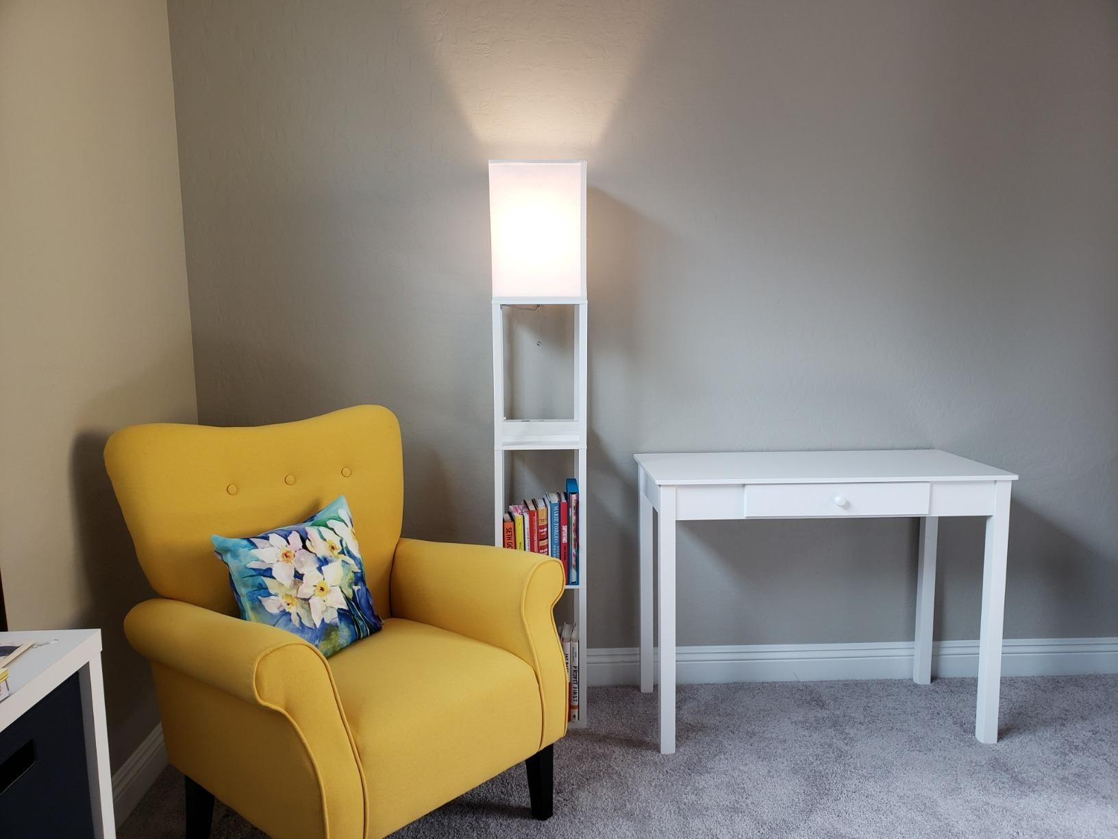 reviewer image of the white brightech maxwell charger shelf floor lamp turned on in a reading nook next to a yellow armchair