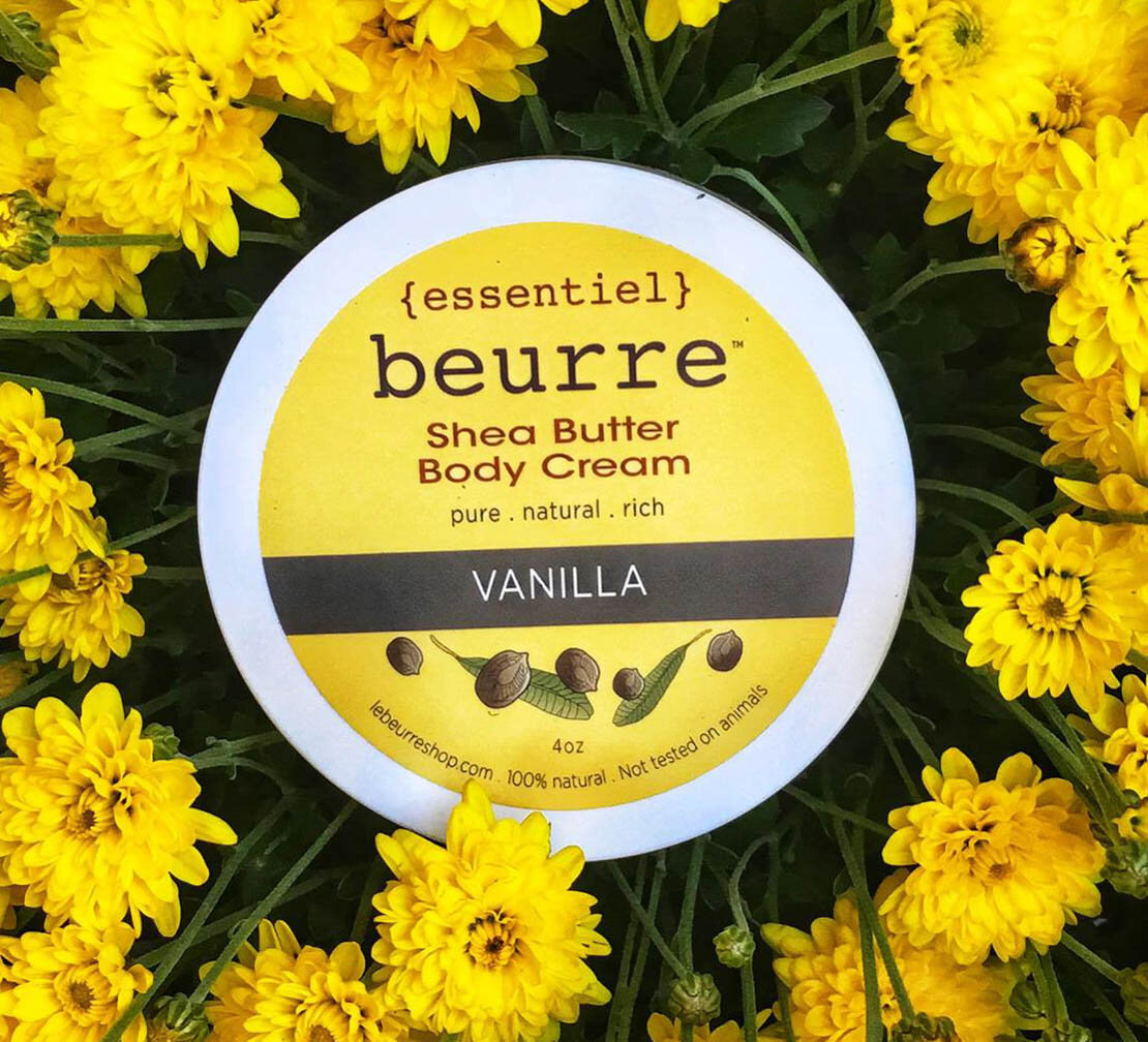 the jar of shea butter body cream on top of yellow flowers