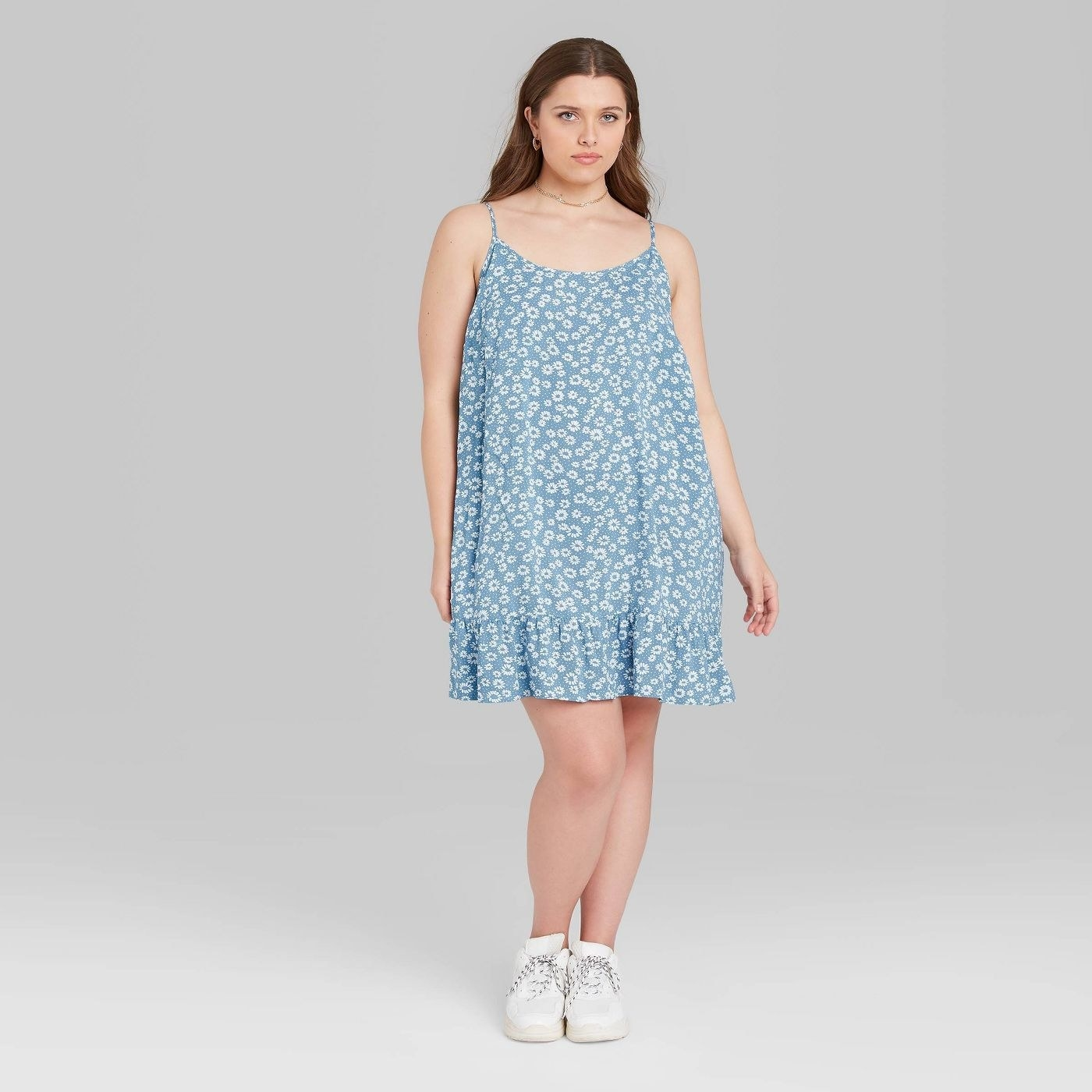 Model wearing light blue sundress with white floral pattern