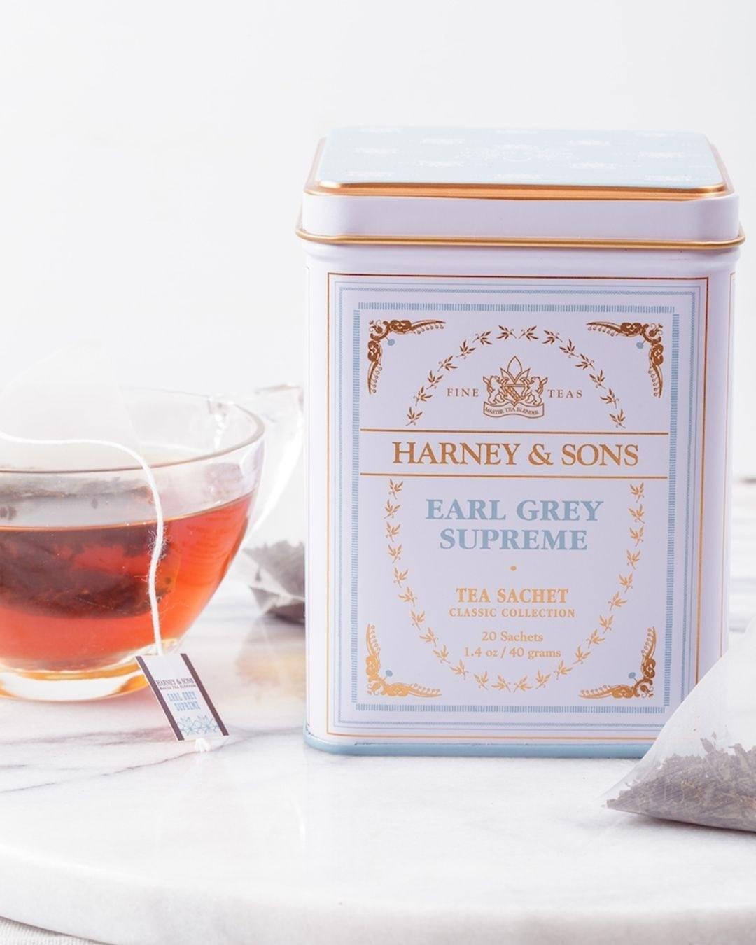 A close up of the tin of Earl Grey Supreme tea next to a glass mug