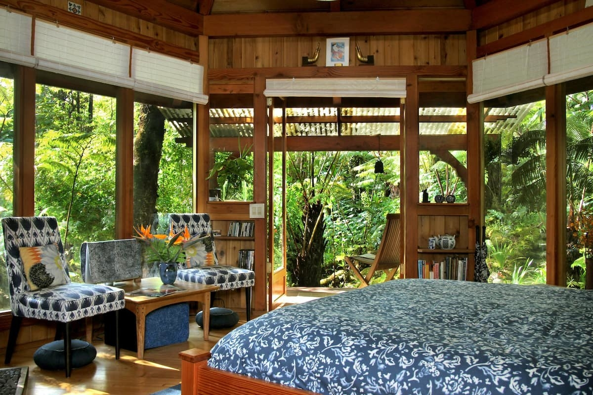 bedroom with glass walls looking out onto a rainforest