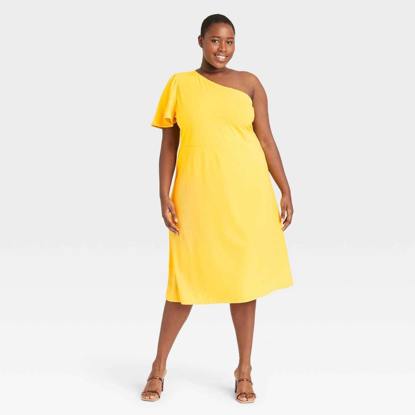 Model wearing yellow dress that goes past the knees