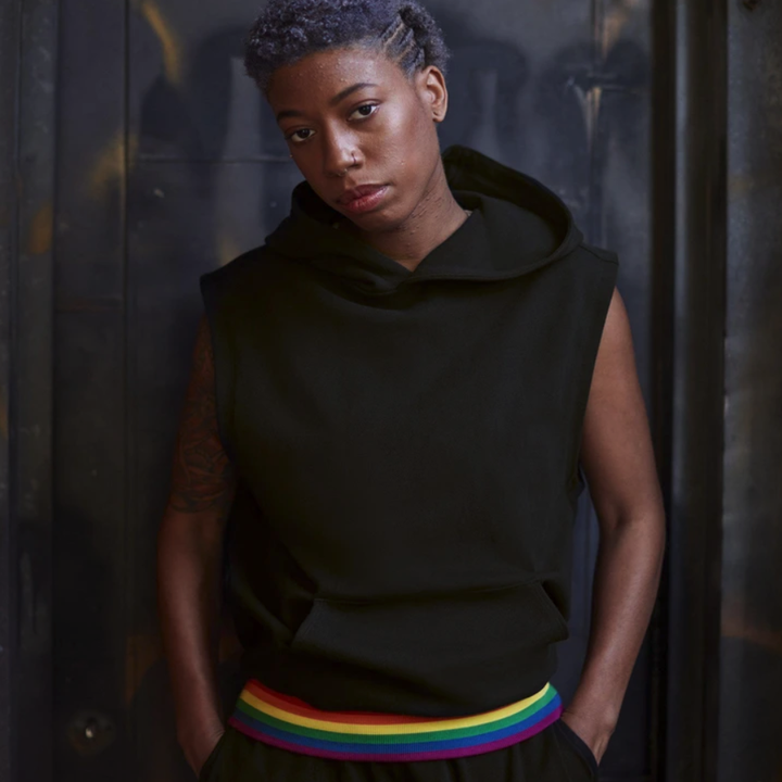 model wearing the black sleeveless hoodies with a rainbow band at the bottom