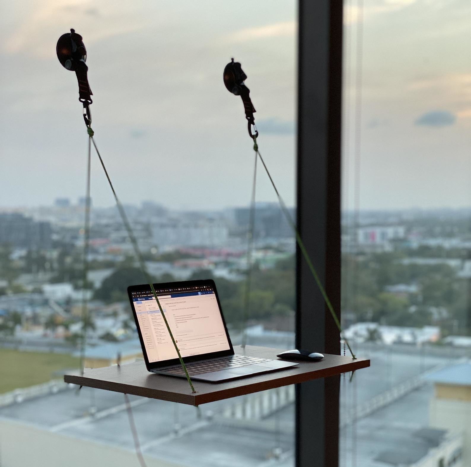 a laptop sits on the hanging window desk