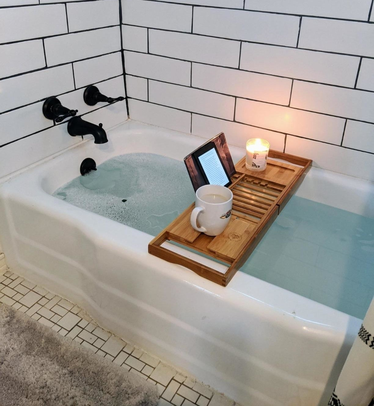 wooden caddy stretched over a tub holding a propped-up kindle, a candle, and a mug