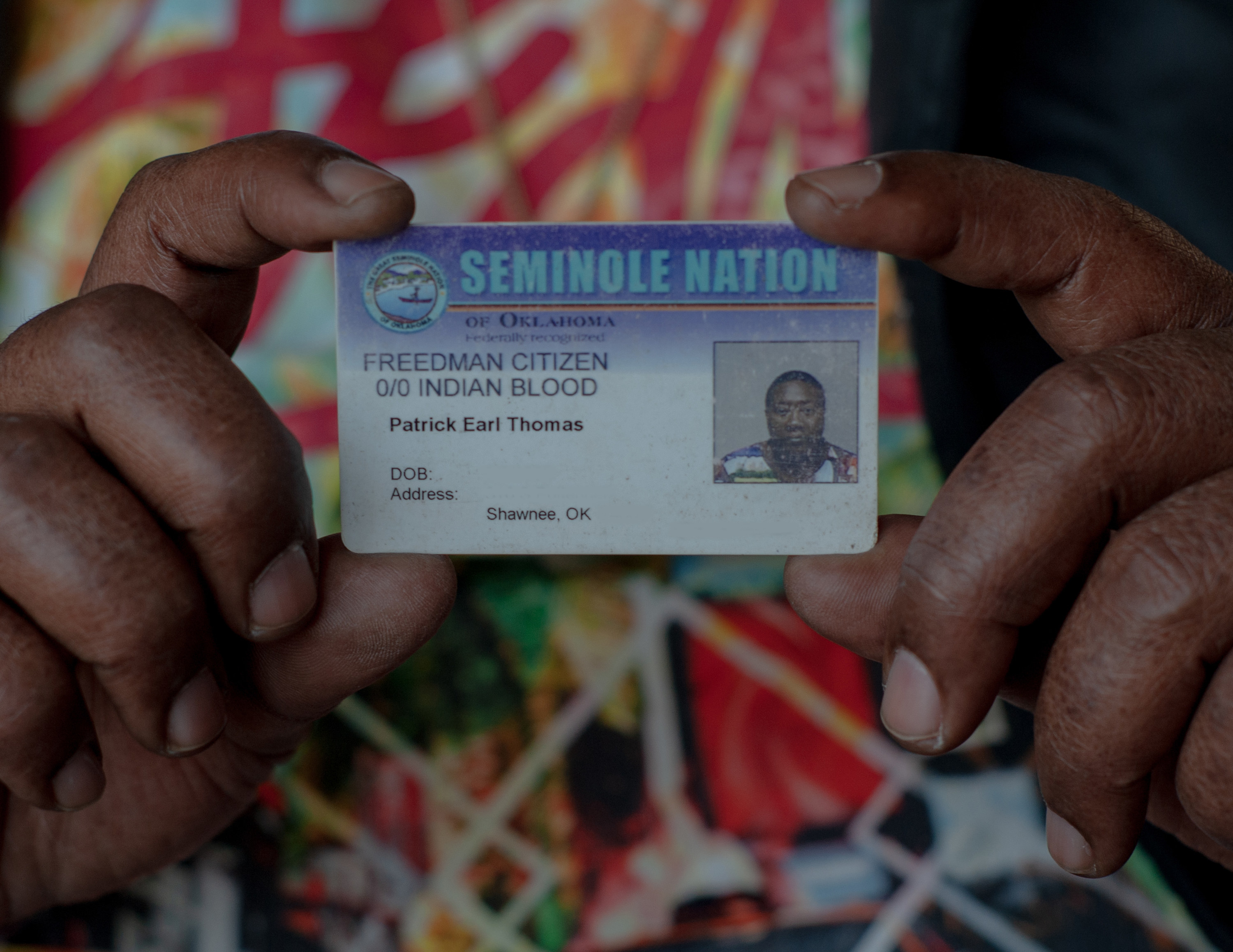 "Patrick Earl Thomas holds up his ID card, which says ""Freedman Citizen, 0/0 Indian Blood"""