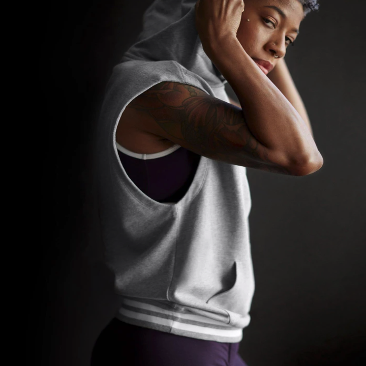 model wearing the gray sleeveless hoodie
