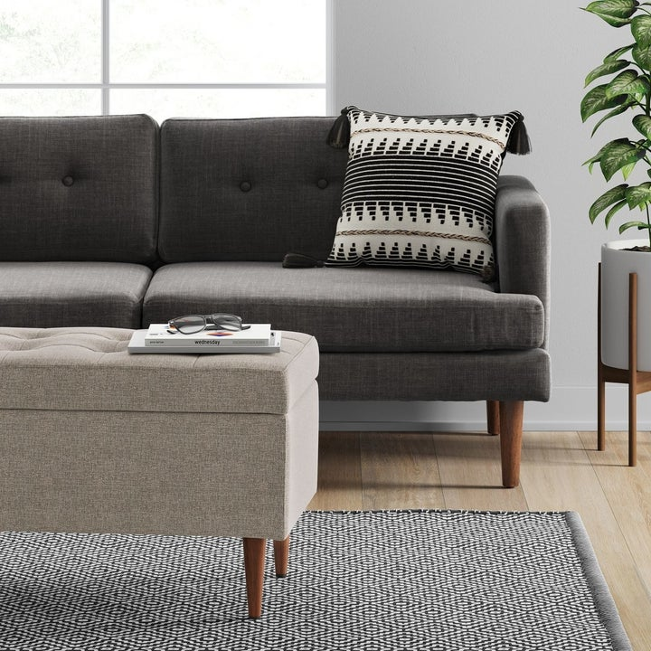 gray storage ottoman in front of a couch
