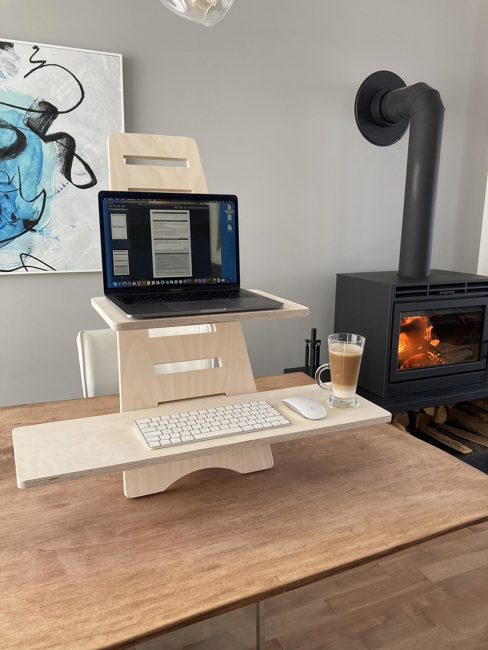 the standing desk on a table with a laptop on the top shelf and a keyboard on the bottom shelf