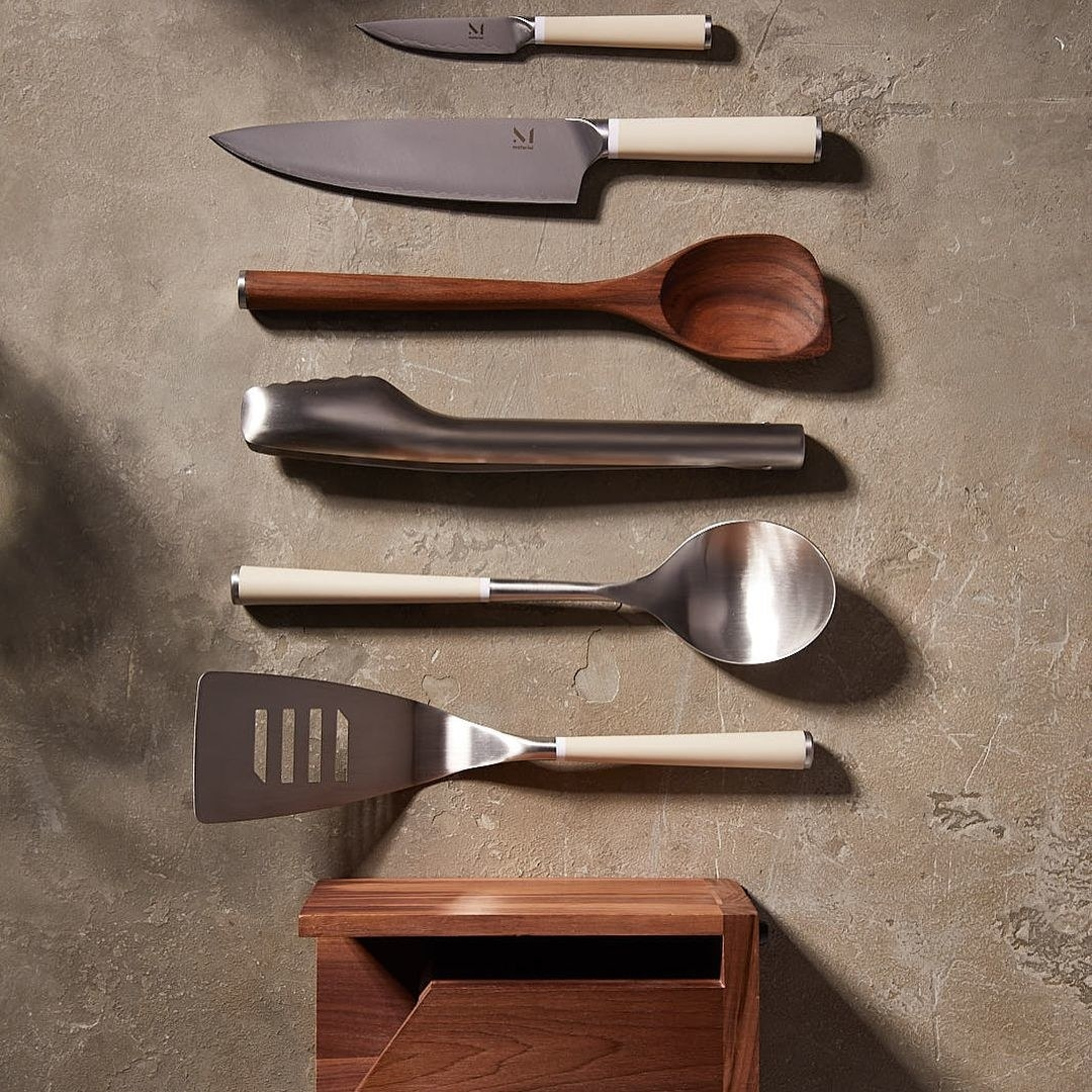 A flatlay of the complete kitchen utensil set on a concrete surface