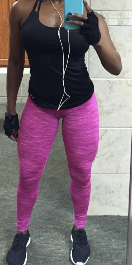 A woman standing in hot pink leggings